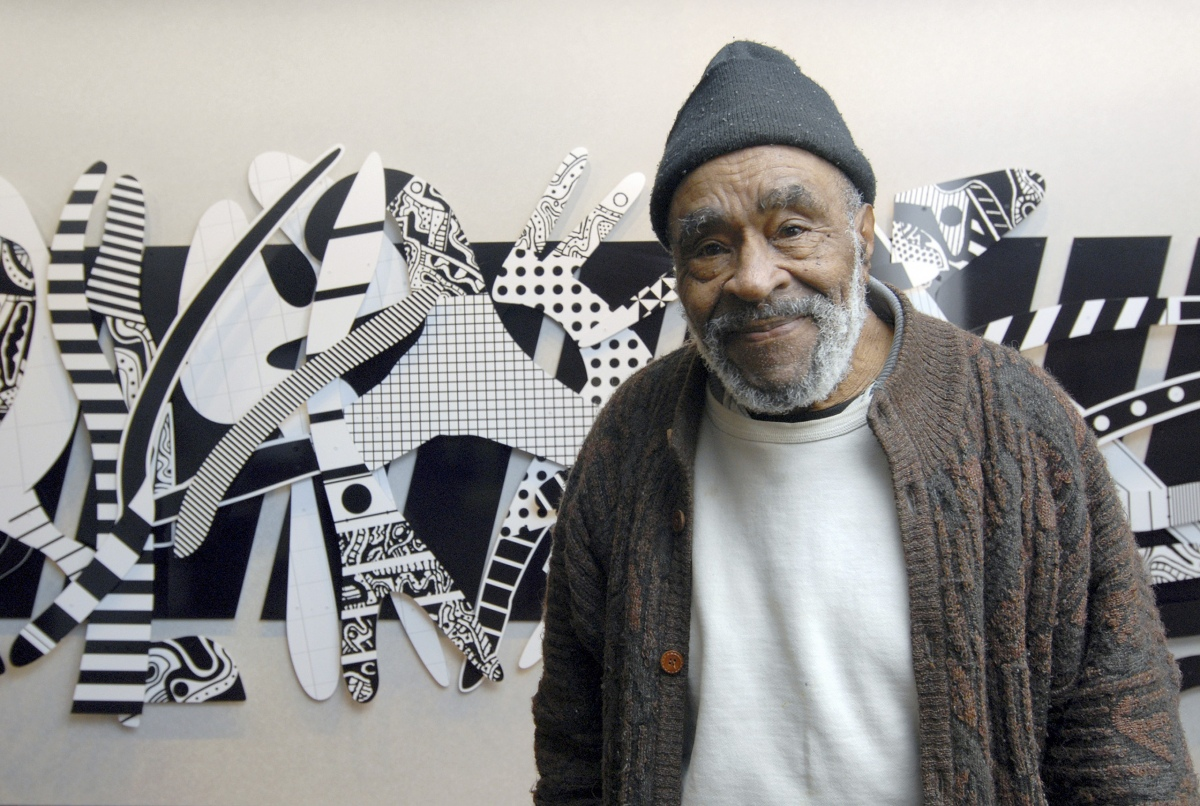 "Charles McGee in front of <em>Regeneration</em>, 2007. Ultraviolet cured inkjet paint on Dibond, 78"" X 264""."