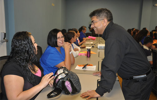 Academy admissions manager Carlos Najera talks with a new student at Good Careers.