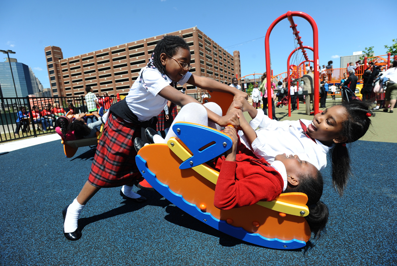 Detroit Edison Public School Academy third grader Lauren Collins, left, pushes her classmates Loren Adams, 9, top right, and Tori Bates, 8, bottom, back and forth on a spring ride.