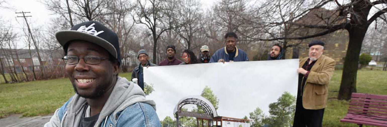 Jamii Tata, president/CEO of Oakland Avenue Artists Coalition, and supporters show their vision for the proposed Moore Community Park.