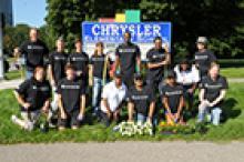 Chrysler team poses in front of Chrysler Elementary School sign
