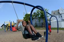 Young african american boy on swing in playground