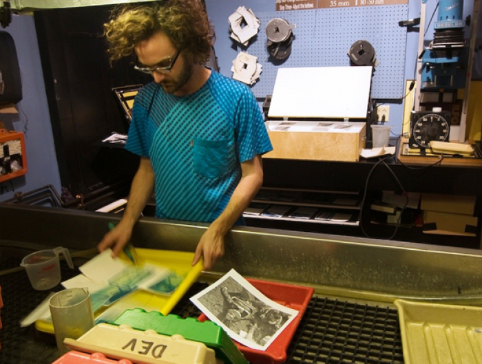 young male working inside of a darkroom