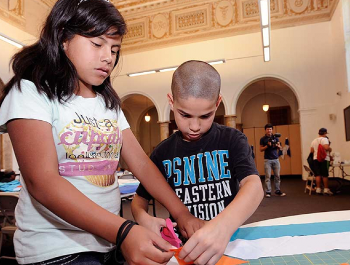 Kids cut out pieces of cloth they want to use during a workshop inside the former Cooper Public Library in Camden, N.J.