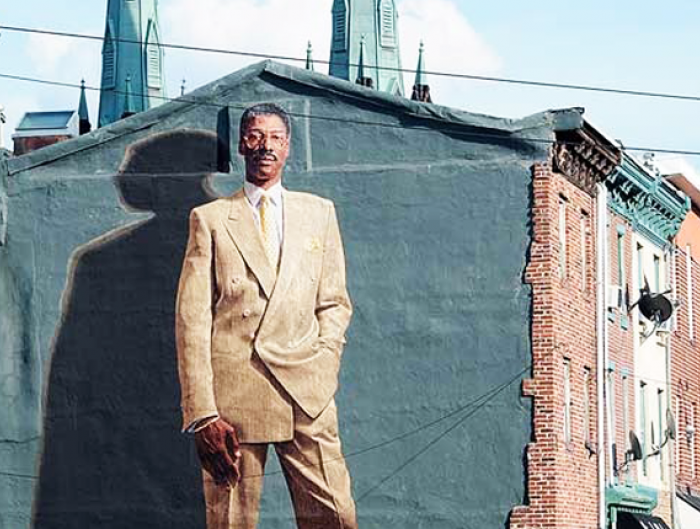 """Dr. J"" by artist Josh Sarantitis towers over Philadelphia residents passing by the mural of the beloved National Basketball Association star Julius Irving."
