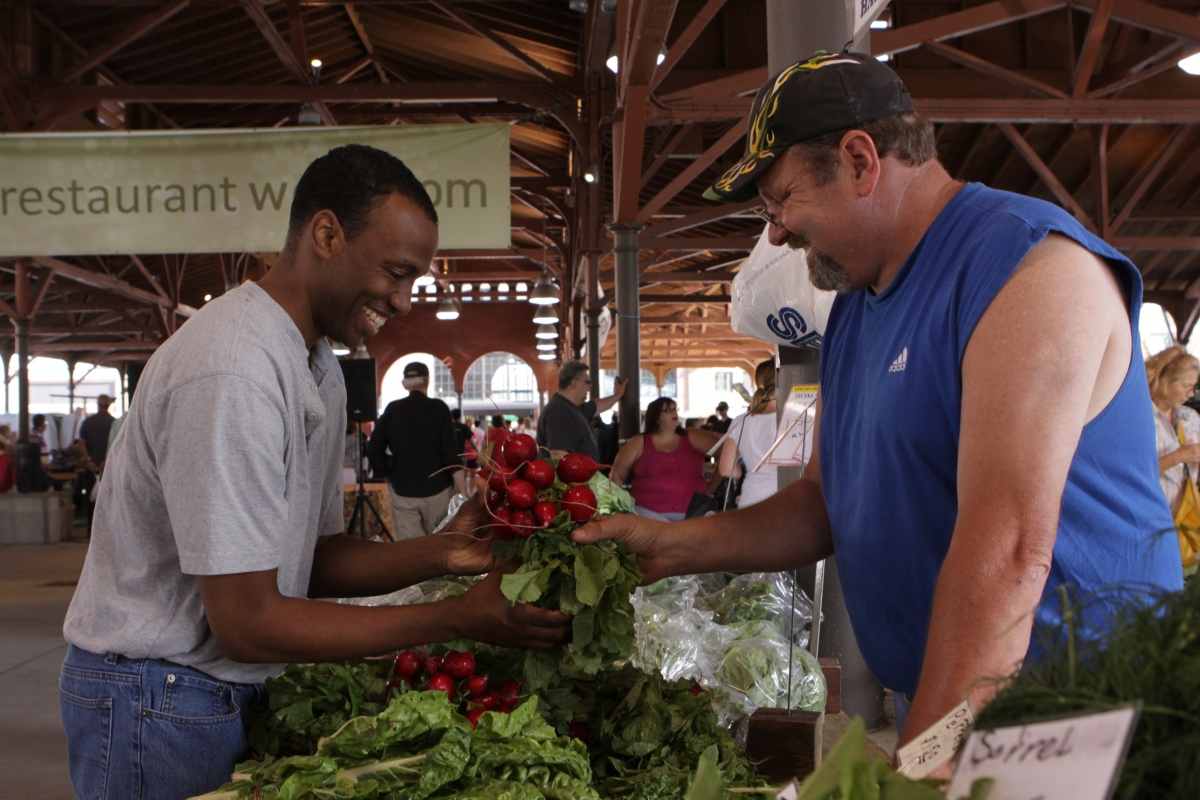 A shopper buys fresh radishes from a vendor at Eastern Market in Detroit. The market participates in the Fair Food Network's Double Up Food Bucks program, which allows shoppers who receive assistance through the federal Supplemental Nutrition Assistance Program, or SNAP,  to stretch their dollars by matching the amount they spend on fresh fruit and vegetables up to $20.