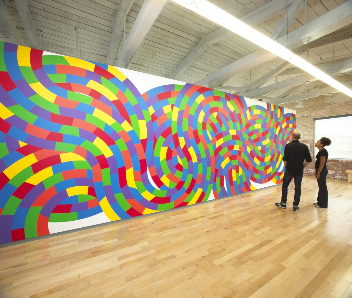 "Visitors examine one of the large-scale wall drawings from ""Sol LeWitt: A Wall Drawing Retrospective"" at the Massachusetts Museum of Contemporary Art, MassMoCA."