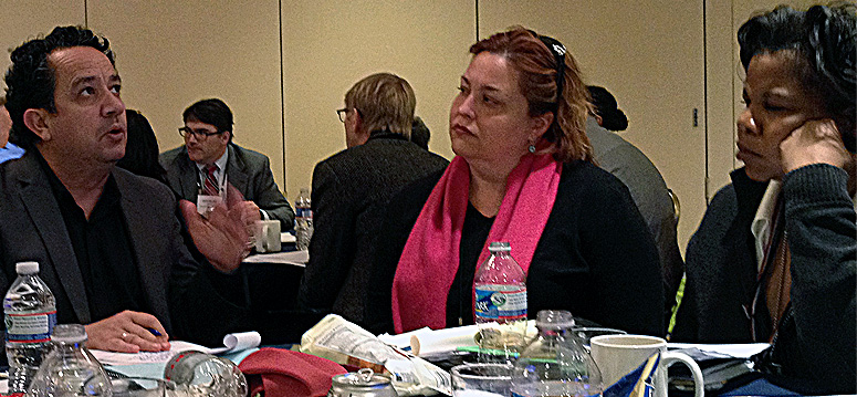Luis Granados, executive director of Mission Economic Development Association in San Francisco, speaks with a group that includes Elizabeth Mason and Angela Dorn, both of the national nonprofit Single-Stop.