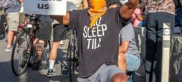 """Protester holds up a sign """"Stop Killing Us"""" at a George Floyd protest on June 7, 2020"""