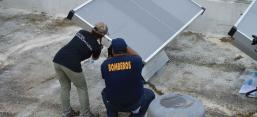 Workers install new solar panels on a building in Puerto Rico after Hurricane Maria.