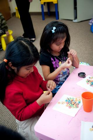 Two young girls putting beads on thread