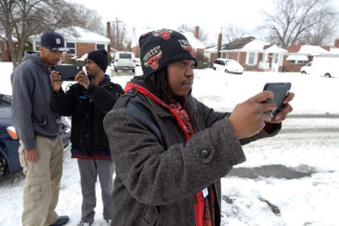 Three young men using cell phones to take photographs of blight in Detroit