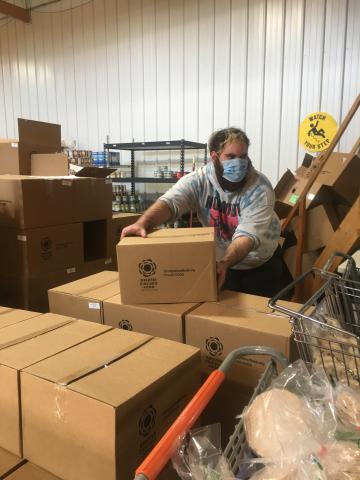A male wearing protective face mask lifts boxes in pantry warehouse setting