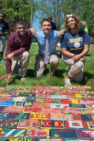 Three people kneeling by a pathway of painted bricks