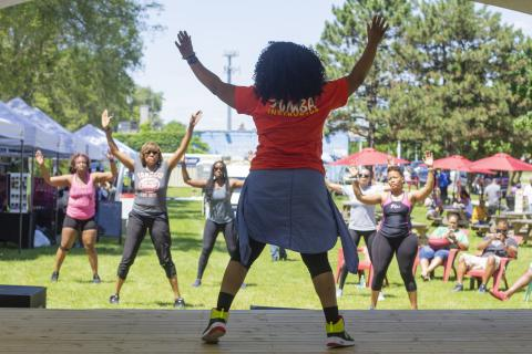 Zumba fitness instructor leads class in outdoor recreation area