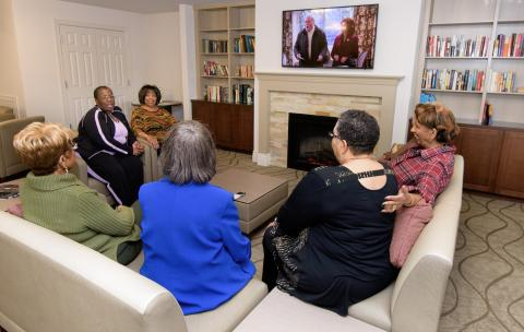 Residents gather to chat and watch TV in the Hartford Village community room