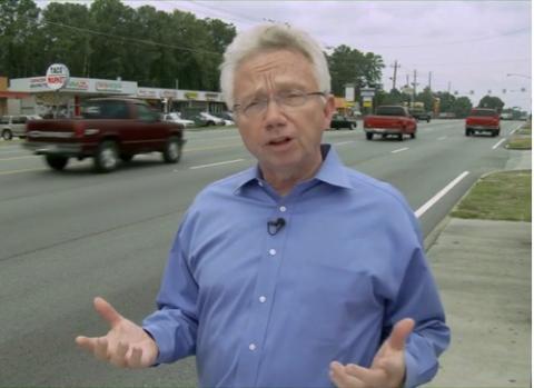 Dr. Richard Jackson talking beside a busy street