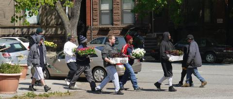 People carry trays of flowers across street