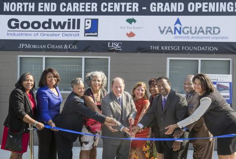 Mike Duggan -- with officials from Goodwill Detroit, Vanguard CDC, Kresge, Detroit LISC and JPMorgan Chase surrounding him -- holds oversize scissors to symboblic ribbon at new North End Career Center