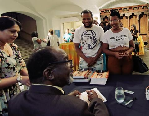 Wendell Harrison autographs monographs for audience members.