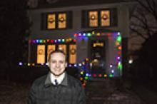 Father standing in front of his home lit by Christmas lights