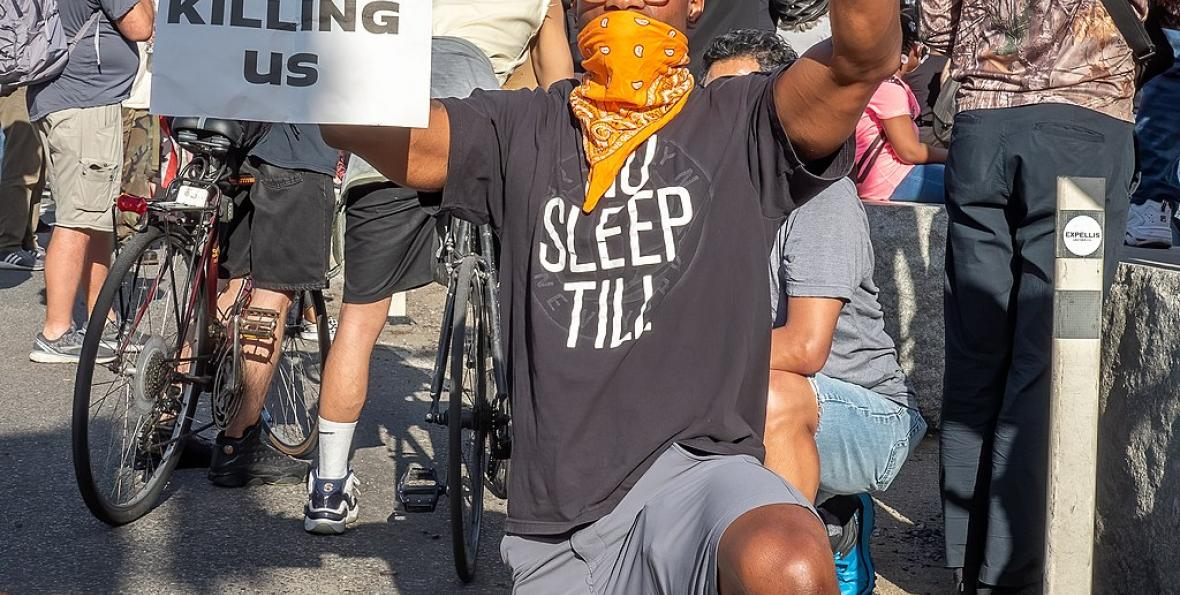 "Protester holds up a sign ""Stop Killing Us"" at a George Floyd protest on June 7, 2020"