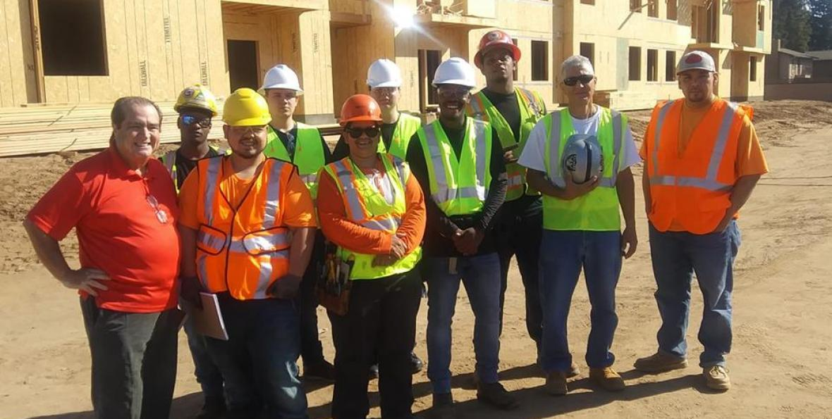 South East Fresno EDC organizes workforce development training, residents pose for photo at construction site wearing hard hats.
