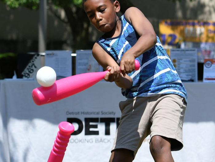 Kingston Brooks, 8, blasts a ball off the tee while playing a little ball on the lawn of the Detroit Public Library during the12th Annual ARISE Detroit! Neighborhoods Day.