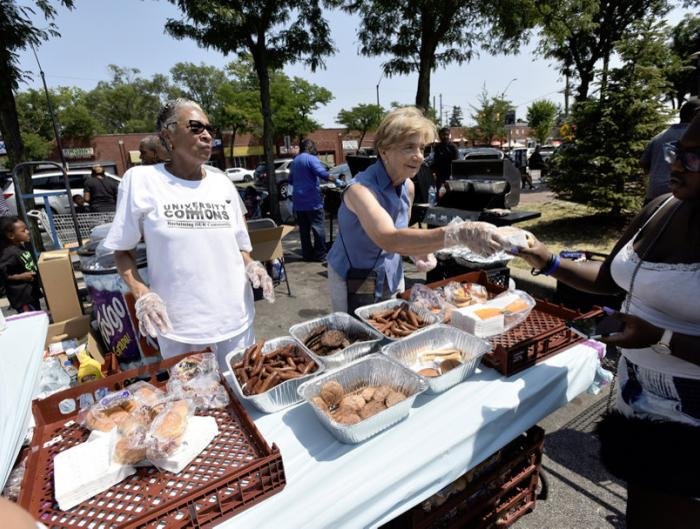 Volunteers hand out free hot dogs and hamburgers in the Mike's Market parking lot during Jazz Extravaganza: Jazz on the Avenue, which was part of the 12th Annual ARISE Detroit! Neighborhoods Day.