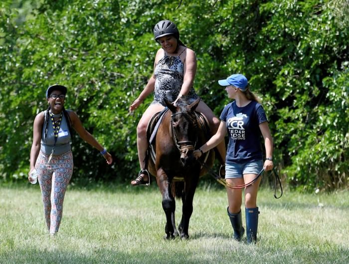 Tangala Howard, North Carolina, on horse, laughs as she pretends to know what she's doing (it was her first time riding a horse) much to the delight of Brianna Brown, left, Detroit, and Mackenzie Pillote, right, Ann Arbor, during the Horse Fair on Linwood Street in Detroit, where novice riders got the chance to experience the joys of riding a horse.