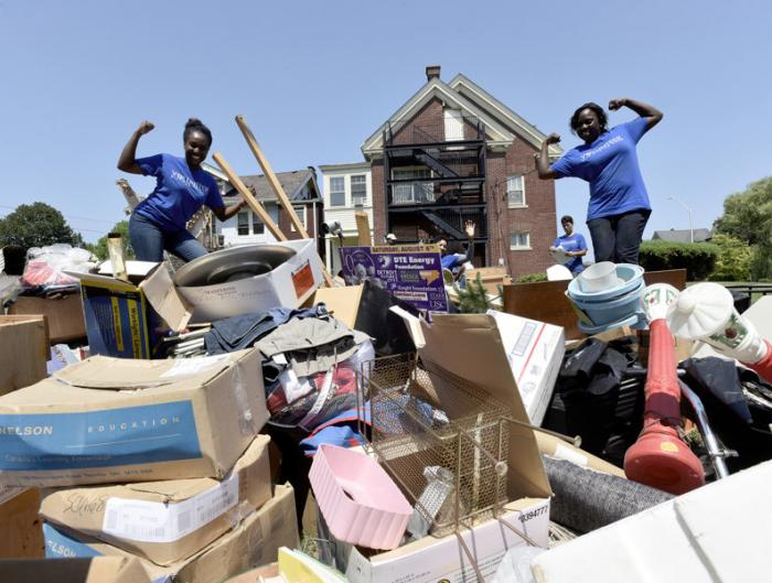 Volunteers from Blue Cross Blue Shield and the Detroit Association of Women's Clubs (DAWC) Inc. pose for a photo near the large pile of junk they had just finished cleaning out the basement of the DAWC building.