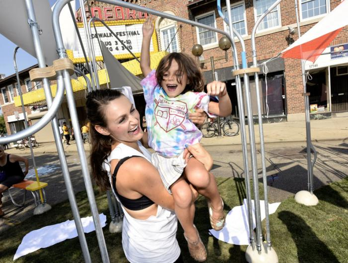 Isabella DeMarco, 5, Detroit, and her mother Tricia, play on one of the installations on the street at the Sidewalk Festival on Detroit's west side during the 12th Annual ARISE Detroit! Neighborhoods Day.