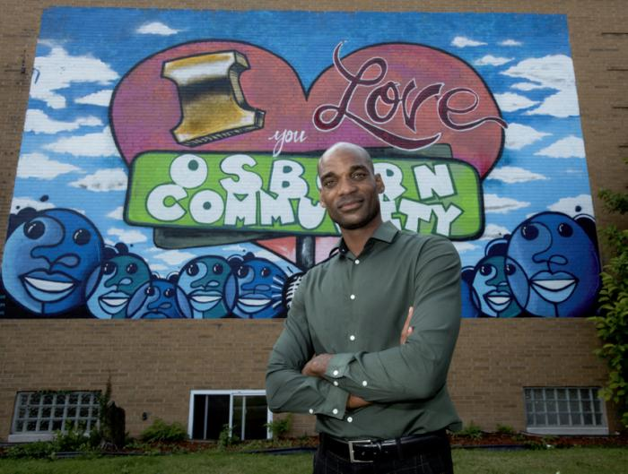 Osborn Neighborhood Alliance leader in front of mural