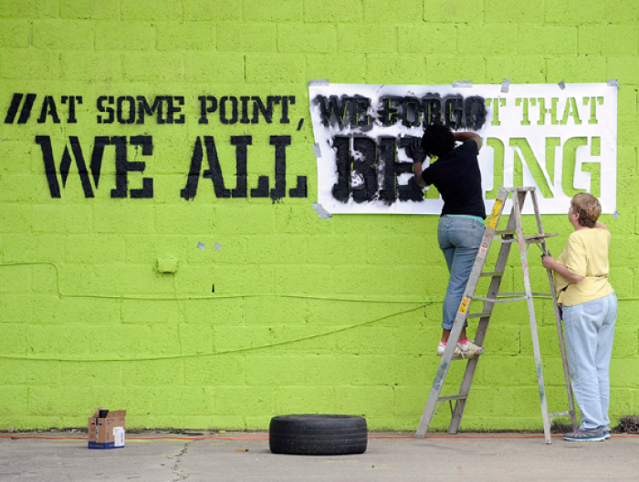 Two women stencil a message on a building a Detroit's East State Fair Avenue