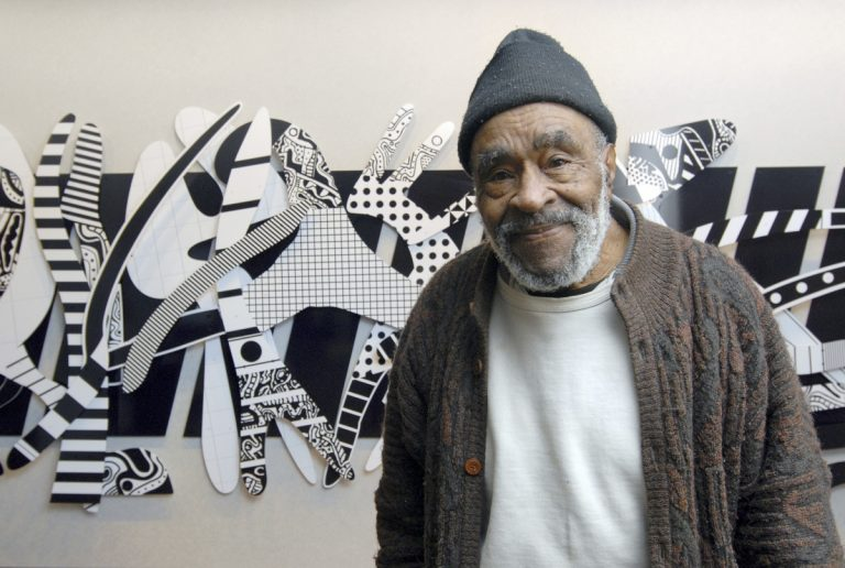 Artist Charles McGee in front of one of his pieces