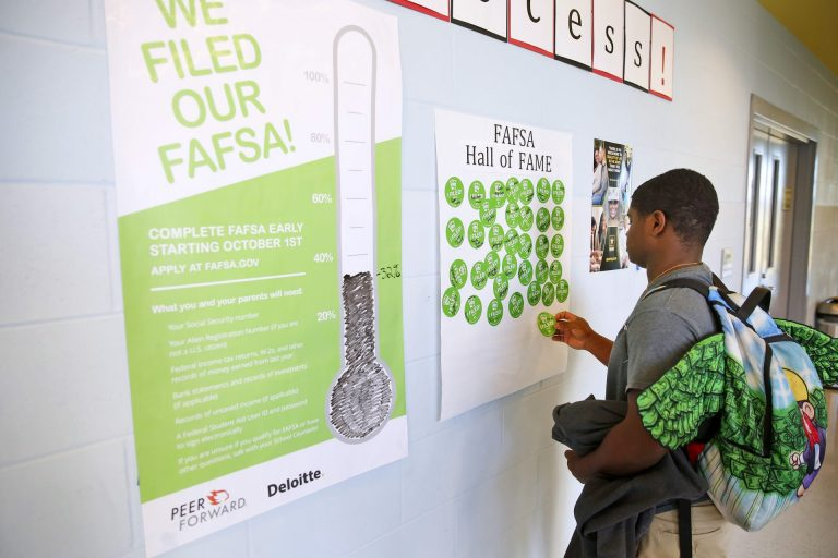 A student stands in front of a wall with two posters. One says that say: 'We Filed our FAFSA' with a picture of a gauge that registers at 32%. The other says 'FAFSA Hall of Fame' and has stickers that say I filed