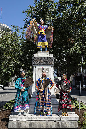 Four Indigenous women surround a marble column that previously displayed a bust of Christopher Columbus in downtown Detroit.