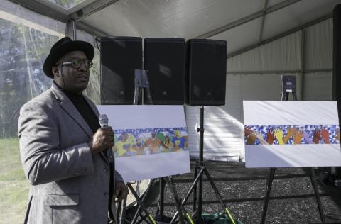 Artist Hubert Massey, holds microphone, by renderings of his park murals