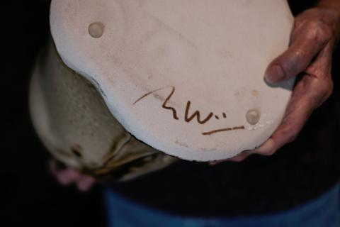 Marie Woo showing signature on piece