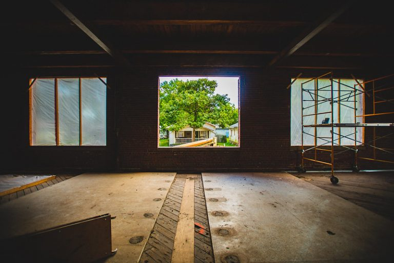 A open window sframes a suburban house and neighborhood from inside a construction project.