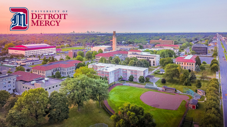 Aerial photo of University of Detroit Mercy campus, downtown skyline in the distance, with pink sky of sunrise