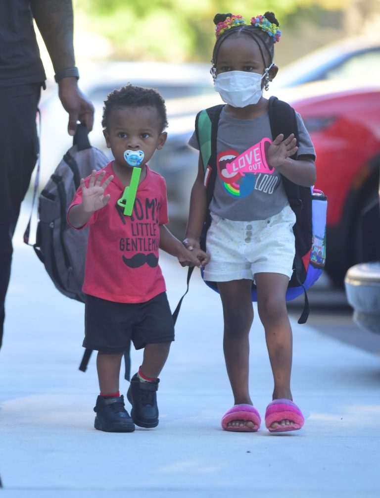 One child with a pacifier in mouth, older child holding his hand, adult walking alongside, mostly out of frame, holding someone's backpack.