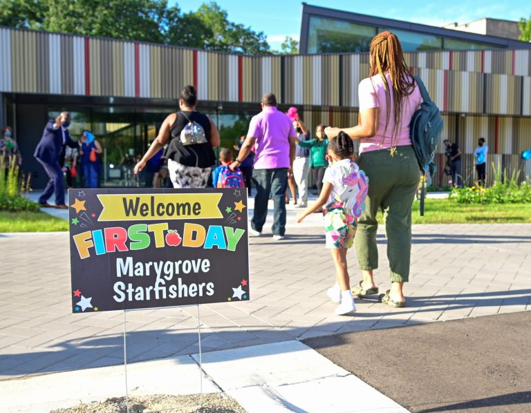 """Lawn sign reads """"Welcome First Day Marygrove Starfishers."""" Parents and children walk by to childcare center on sunny day."""
