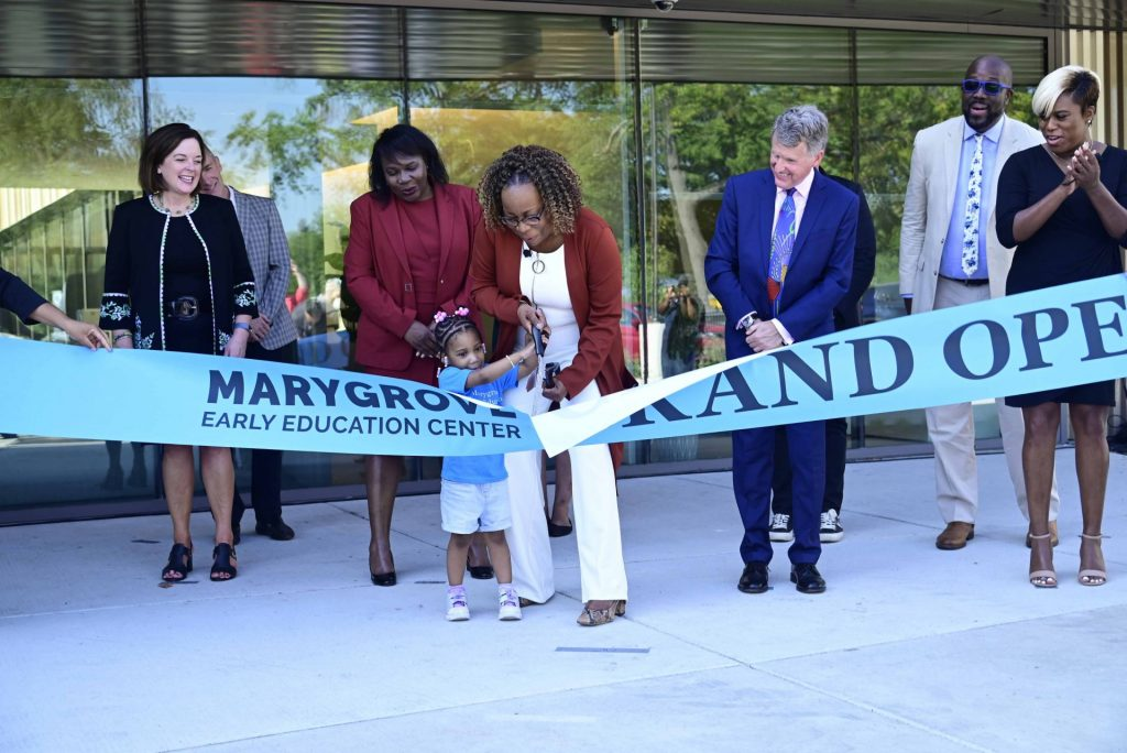 Small child and school principal cut the ribbon for the grand opening of the Marygrove Early Education Center