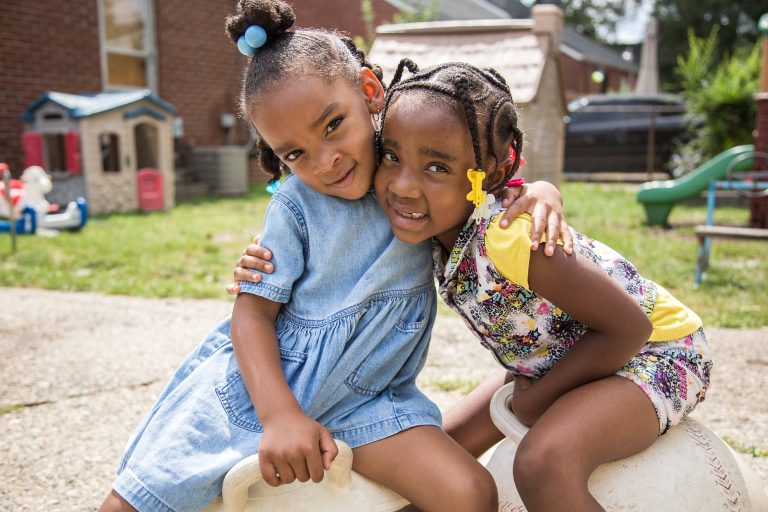 Two little girls hug outdoors at a childcare center.