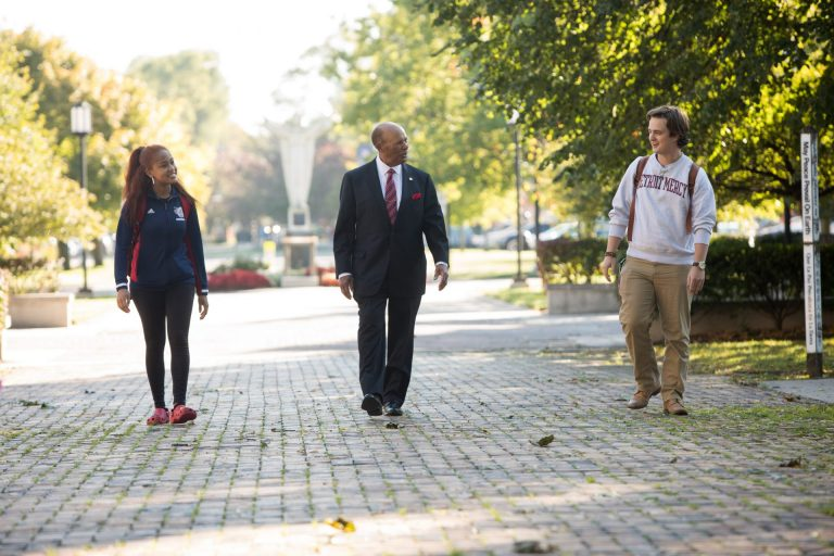 University of Detroit Mercy President Dr. Antoine Garibaldi walks on campus flanked by a student on either side.