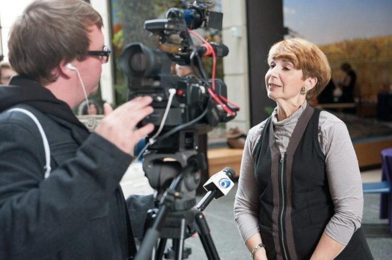 Photo of Gilda Jacobs being interviewed by TV news reporter.