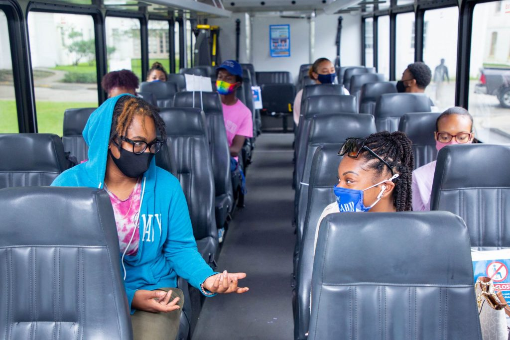 Dillard University students ride a campus shuttle.)
