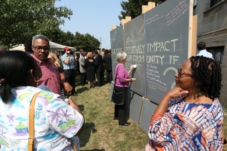 Attendees at the launch of the Live6 Alliance leave messages of hope for the community on a large outdoor blackboard.