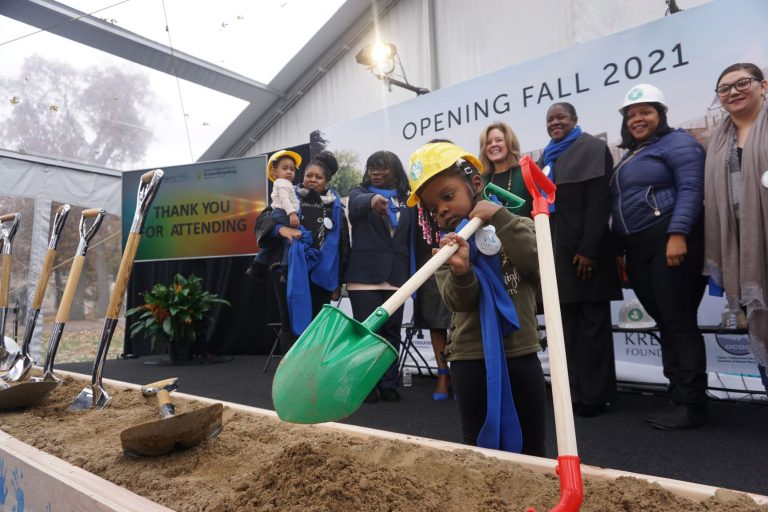 Small child with toy shovel while adults look on at groundbreaking for Early Childhood Education center on grounds of Marygrove Conservancy in Northwest Detroit